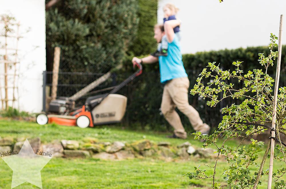 Wochenende in Bildern - Mann mäht mit Kleinkind den Rasen